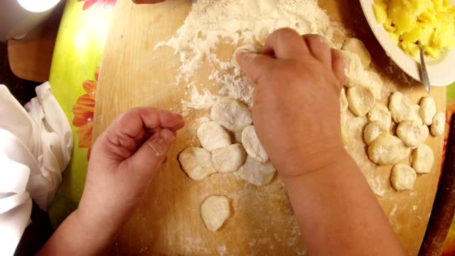 On Board Sliced Pieces of Paste and Hands Cut Dough Technique of Cooking Traditional Ukranian Meal Vareniks with Potatoes at Home Close Up ravioli stock videos & royalty-free footage
