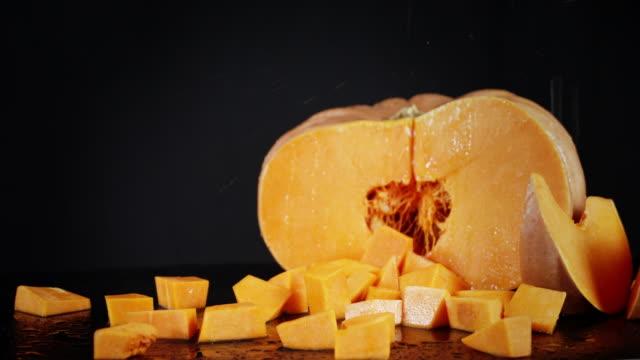 On chopped pieces of ripe pumpkin falling water drops.