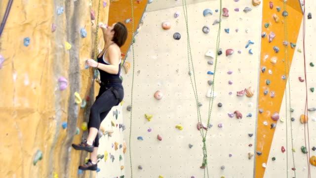 auf klettern frau ist an wand im fitness-studio während der übung angespannt - bouldering stock-videos und b-roll-filmmaterial