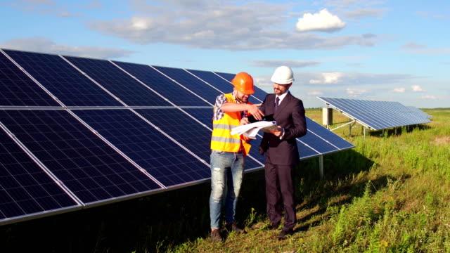En material de archivo capataz y la empresas cliente en el campo en la estación de energía solar. - vídeo