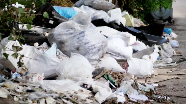on ground, on side of road, lots of garbage is lying. scattered trash, rubbish, old things, car tires, broken glass, plastic. garbage dump. ecology, pollution of the environment - mucchio video stock e b–roll