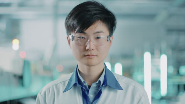on high-tech factory: portrait of asian worker wearing uniform and safety goggles. in the background blurred electronics assembly line with bright lights. - occhiali protettivi video stock e b–roll