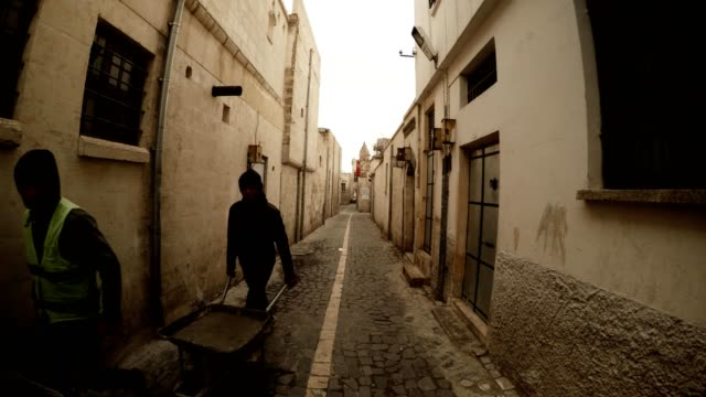 On Narrow Ancient Street Paved With Stones Workers With Wheelbarrow Urfa video
