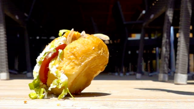on sunny day hamburger with sauce falls to floor in cafe, slow motion video