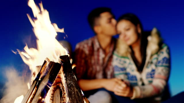 On the beach, lit a fire in the background blurred young couple embracing - video