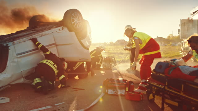 On the Car Crash Traffic Accident: Paramedics and Firefighters Rescue Injured Trapped Victims. Medics give First Aid to Female on Stretchers. Firemen Use Hydraulic Cutters Spreader to Open Vehicle On the Car Crash Traffic Accident: Paramedics and Firefighters Rescue Injured Trapped Victims. Medics give First Aid to Female on Stretchers. Firemen Use Hydraulic Cutters Spreader to Open Vehicle stretcher stock videos & royalty-free footage