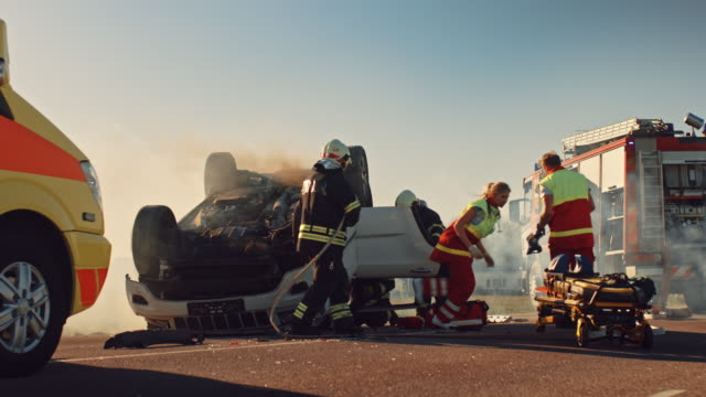 na miejscu wypadku samochodowego: ratownicy medyczni i strażacy ratują rannych poszkodowanych uwięzionych w pojeździe. medycy używają noszy, wykonują pierwszą pomoc. strażacy chwycić sprzęt z fire engine - first responders filmów i materiałów b-roll