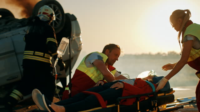 On the Car Crash Traffic Accident Scene: Paramedics Save Life of a Passenger Lying on Stretchers. They Listen To a Heartbeat, Use Oxygen Mask, setup Drop Counter. Firefighters Use Cutters to Open Car On the Car Crash Traffic Accident Scene: Paramedics Save Life of a Passenger Lying on Stretchers. They Listen To a Heartbeat, Use Oxygen Mask, setup Drop Counter. Firefighters Use Cutters to Open Car stretcher stock videos & royalty-free footage