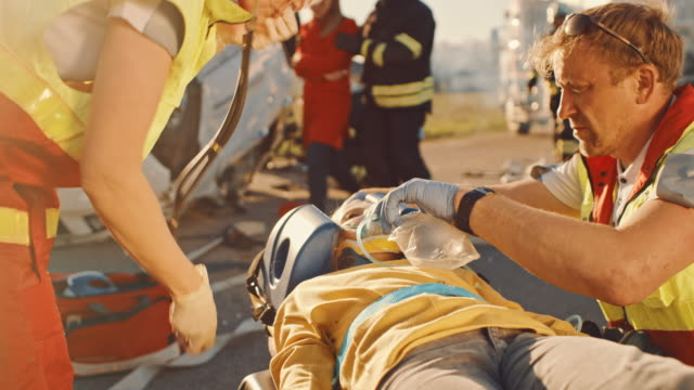 On the Car Crash Traffic Accident Scene: Paramedics Saving Life of a Traffic Accident Victim who is Lying on Stretchers. They Listen To a Heartbeat, Apply Oxygen Mask and Give First Aid Help video