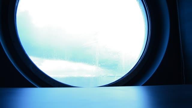 på glaset runt hyttventil av fartyget strömmande vatten, stänk från vågorna. bakgrunden blå - lucia bildbanksvideor och videomaterial från bakom kulisserna