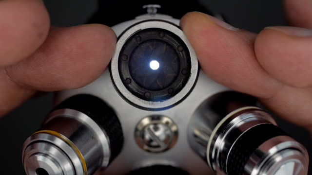 On the microscope lens, manually close (open) the diaphragm to correct exposure On the microscope lens, manually close (open) the diaphragm to correct exposure and increase (reduce) the depth of field. Bottom view. Macro. Closeup. Shallow depth of field microscope stock videos & royalty-free footage