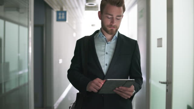 On the move Businessman walking in hallway.  He stops. He is using digital tablet and then he walks away. surfing the net stock videos & royalty-free footage