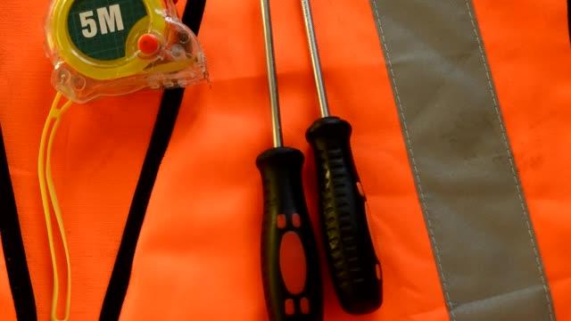 på den orangefärgade konstruktionen västen är skruvmejsel konstruktions verktyg, måttband, skift nyckel, labor dag koncept - lucia bildbanksvideor och videomaterial från bakom kulisserna
