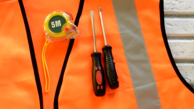 vídeos y material grabado en eventos de stock de en el chaleco de construcción naranja son herramientas de construcción de destornillador, cinta de medición, llave inglesa, concepto de día laboral - día del trabajo