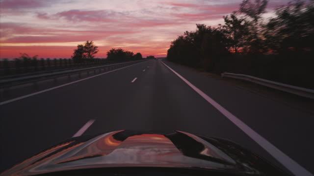 vídeos de stock, filmes e b-roll de na estrada ao pôr do sol. - estrada principal estrada