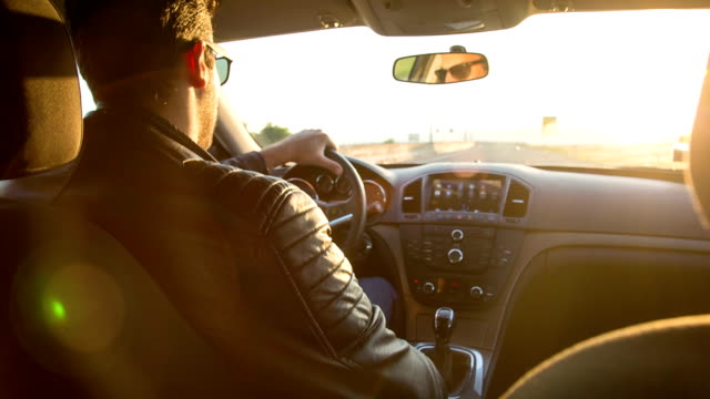 On The Road Handsome young man driving a sports car. We can see the road and the vehicle interior: a steering wheel, sports car stock videos & royalty-free footage