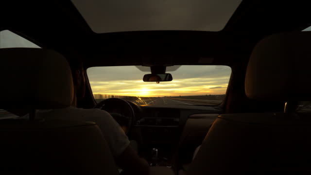 On the road. Couple in the car travelling at sunset. Is always a pleasure to drive at sunset. luxury car stock videos & royalty-free footage