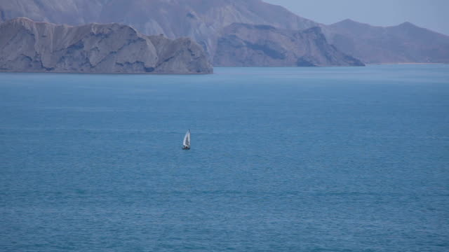 On the sea a lonely sailboat sails video
