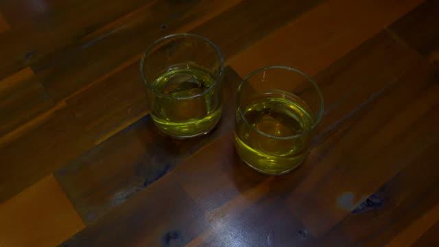 vidéos et rushes de sur la table sont les verres avec du thé vert. main d'une femme prend un verre - pots de bureau
