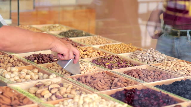 On the wooden counter, the seller offers nuts and dried fruits video