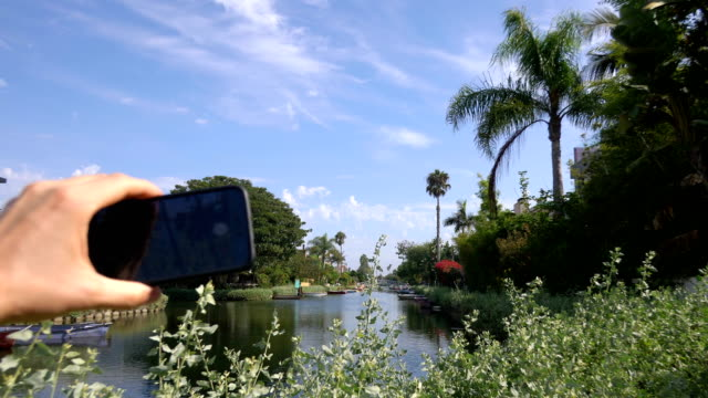 POV on Tourist Photographing Los Angeles Venice Canals in 4K Slow motion 60fps video