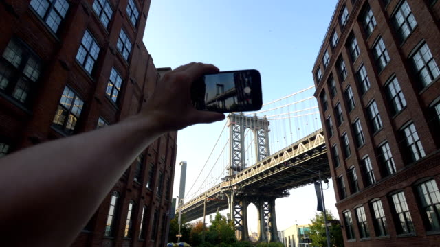 POV on Tourist Photographing Manhattan Bridge in Dumbo NYC in 4K Slow motion 60fps video