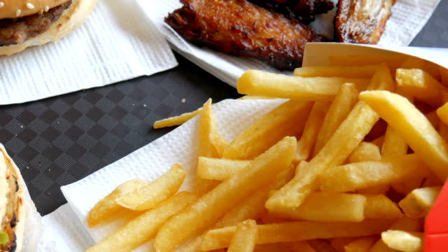 on tray is fast food. not healthy food on the table burgers, french fries and fried chicken wings - cheeseburger filmów i materiałów b-roll