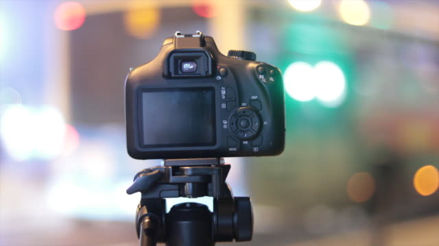 dslr on tripod recording bokeh of city traffic lights. video production. - bokeh stock videos & royalty-free footage