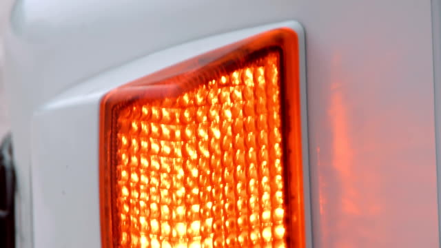 On white truck the orange turn signal flashes bright light