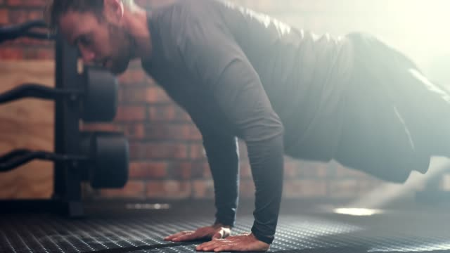 Once you get into shape, stay that way! 4k video footage of a young man doing push-ups at the gym push ups stock videos & royalty-free footage