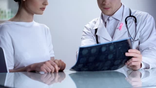 Oncologist informing woman about no threat of breast cancer, both smiling Oncologist informing woman about no threat of breast cancer, both smiling mammogram stock videos & royalty-free footage