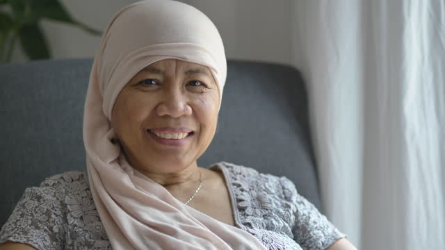 Oncology Patient Senior woman with cancer sitting in her home wearing a headscarf on the road to recovery. filipino ethnicity stock videos & royalty-free footage