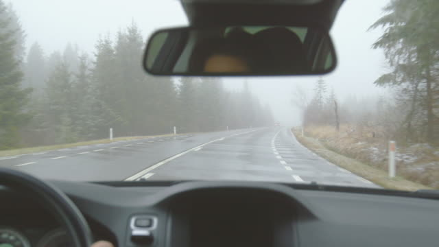 oncoming traffic - driving on a mountain road on a foggy winter day - pov shot - hand held camera - ноябрь стоковые видео и кадры b-roll