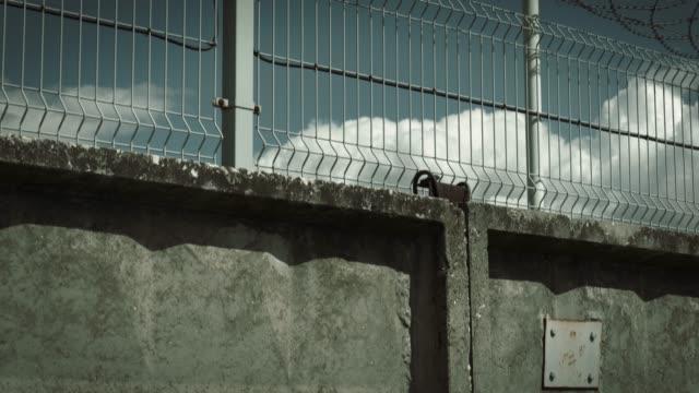 oncrete fence, barbed wire and surveillance camera - prigione video stock e b–roll