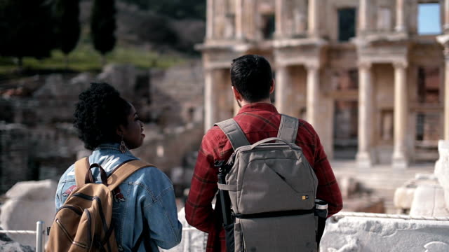 One african woman and one white man visits Ephesus ancient city in selcuk izmir. video