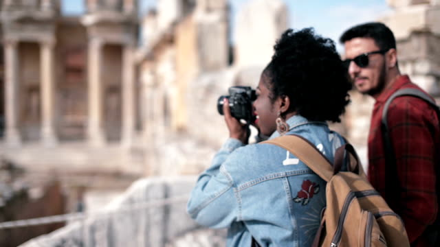 One african woman and one white man visits Ephesus ancient city. video