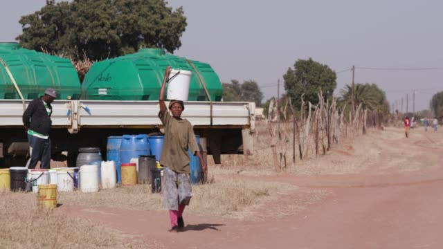 one african woman collecting water from a  tanker, balancing bucket on her head and walking back to her home - republika południowej afryki filmów i materiałów b-roll