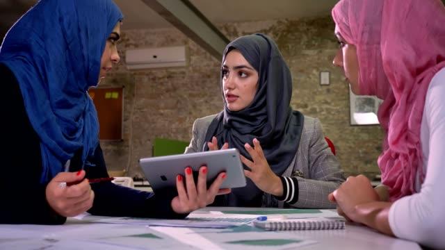 en arabisk kvinna i blå hijab pekar på andra muslimska tjejer i tablett, arbetsgrupp humör, samtal med kollegor, sittande och chill, moderna kontor - hijab bildbanksvideor och videomaterial från bakom kulisserna