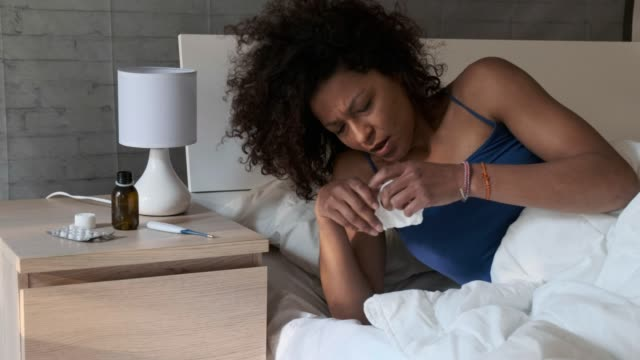One black woman blowing nose in bed Video is about one black woman blowing nose in bed, shot gets slowly closer to the woman shivering stock videos & royalty-free footage