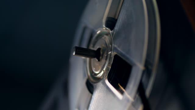 one bobbin slowly spins on a vintage tape player. - bobina apparecchiatura di registrazione del suono video stock e b–roll
