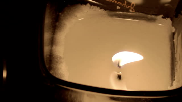 One candle flame at night closeup video