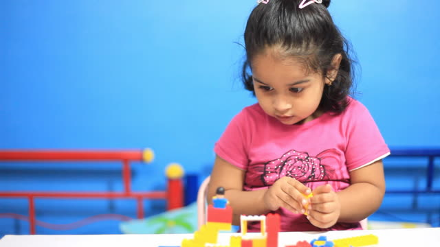 One cheerful Indian little girl playing with blocks video