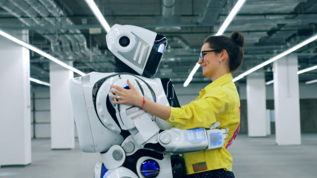 vídeos de stock e filmes b-roll de one droid dances with a woman, while she talks to it. - future hug