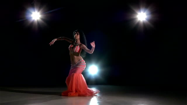 one european woman belly dancer starting dancing on black, back light, slow motion - belly dancing stock videos and b-roll footage