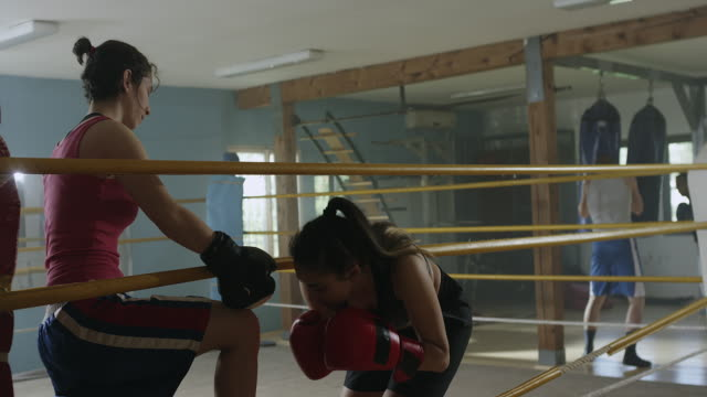 One female boxer helping other to enter in the ring video