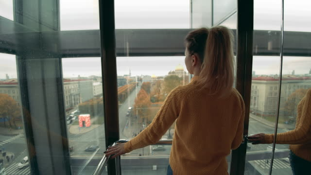 One girl looks at Riga from elevator.
