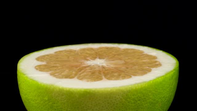 vidéos et rushes de la moitié des fruits verts oroblanco. tournant sur le plateau tournant. isolé sur le fond noir. gros plan. macro. - pamplemousse