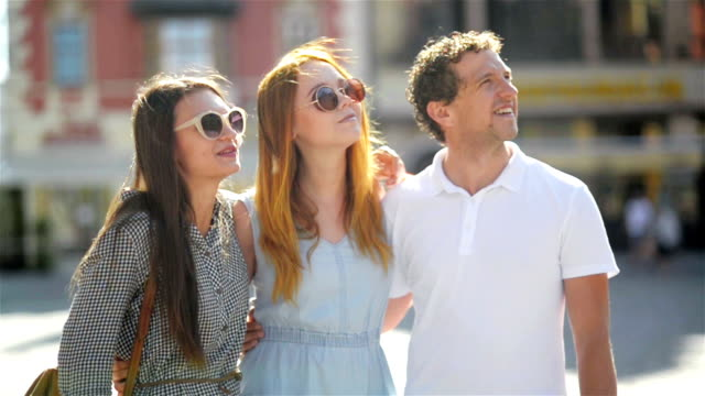 One Handsome Man and Two Attractive Young Girls Talking and Smiling Spending Time Together at the Old City Square in Sunny Warm Day Outdoors video