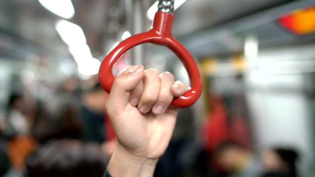 one human hand holding handrail or grip straps in subway or train - parapetto barriera video stock e b–roll