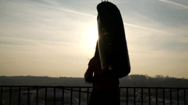 one man punches hard in bag on boxing training, silhouette of boxer, sun shines, sportsman practicing, power training, strong guy hard exercising, strength exercises, workout, handheld, sunny day. - sacco per il pugilato video stock e b–roll